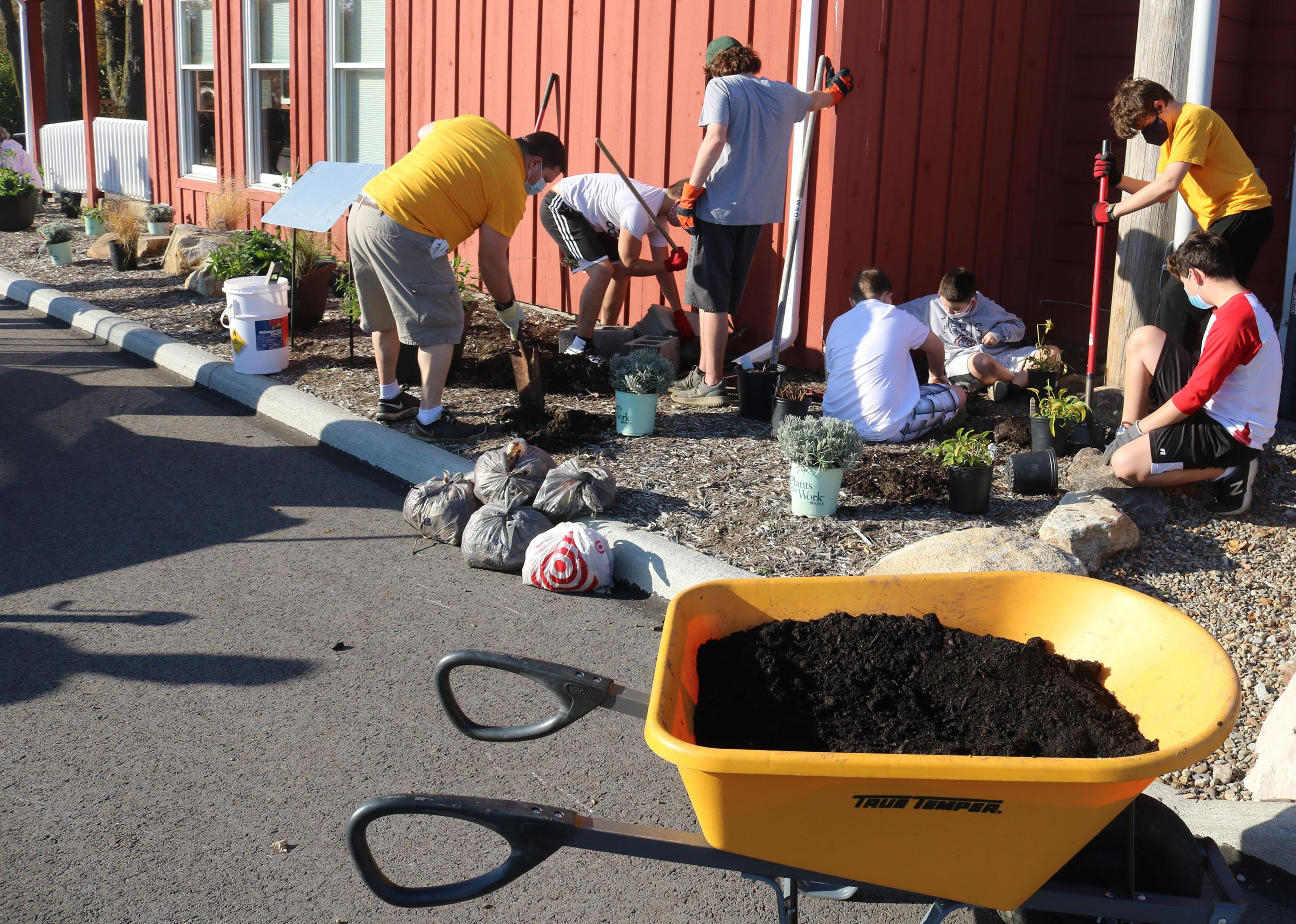 Volunteers work to plant pollinator plants in the Clague Playhouse Pollinator Garden.