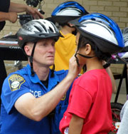 Officer Adjusting a Childs Bicycle Helmet