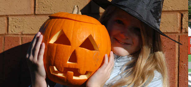 Young Girl in a Witch Costume Holding a Jack-O-Lantern